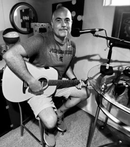 Black and white image of a bald white man with a guitar, sitting on a stool.
